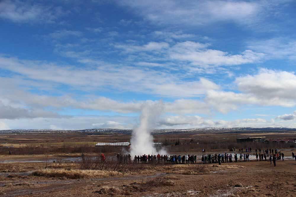 Die Touristen versammeln sich um den Geysir, um dessen Ausbruch mitzuerleben.