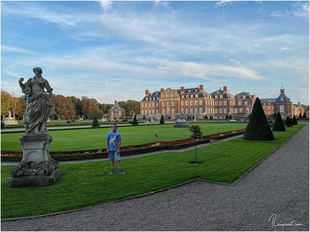 Sohnemann im Schlossgarten neben einer der Statuen