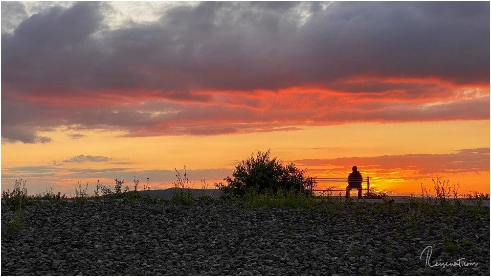 Ein Sonnenuntergang zum genießen und ein zufällig dort sitzender Mann als perfektes Fotomotiv