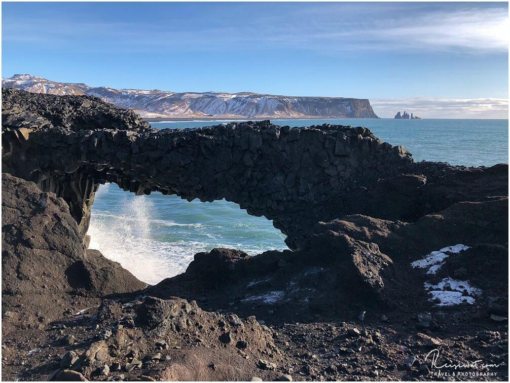 Der Arch im unteren Bereich, im Hintergrund erkennt man gut die drei Felsnadeln bei Reynisfjara
