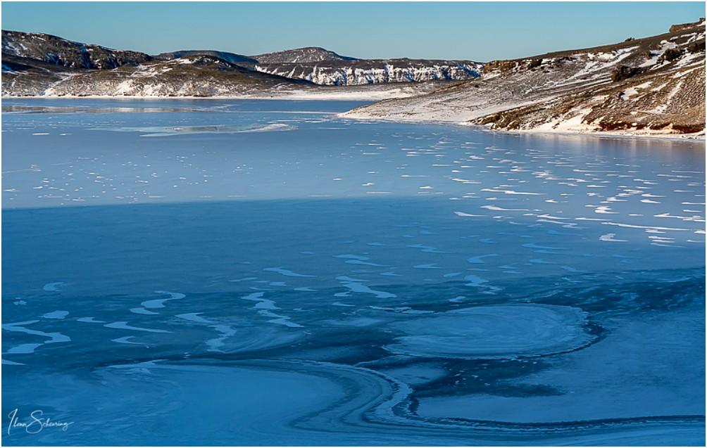 Ein zugefrorener See am Wegesrand