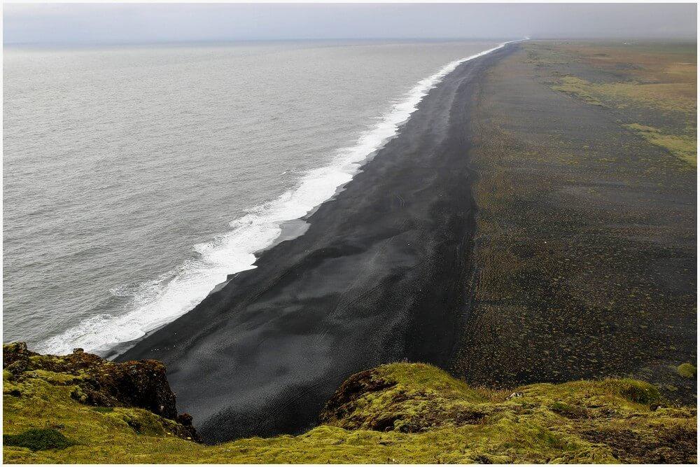 Endlos erscheinender schwarzer Strand