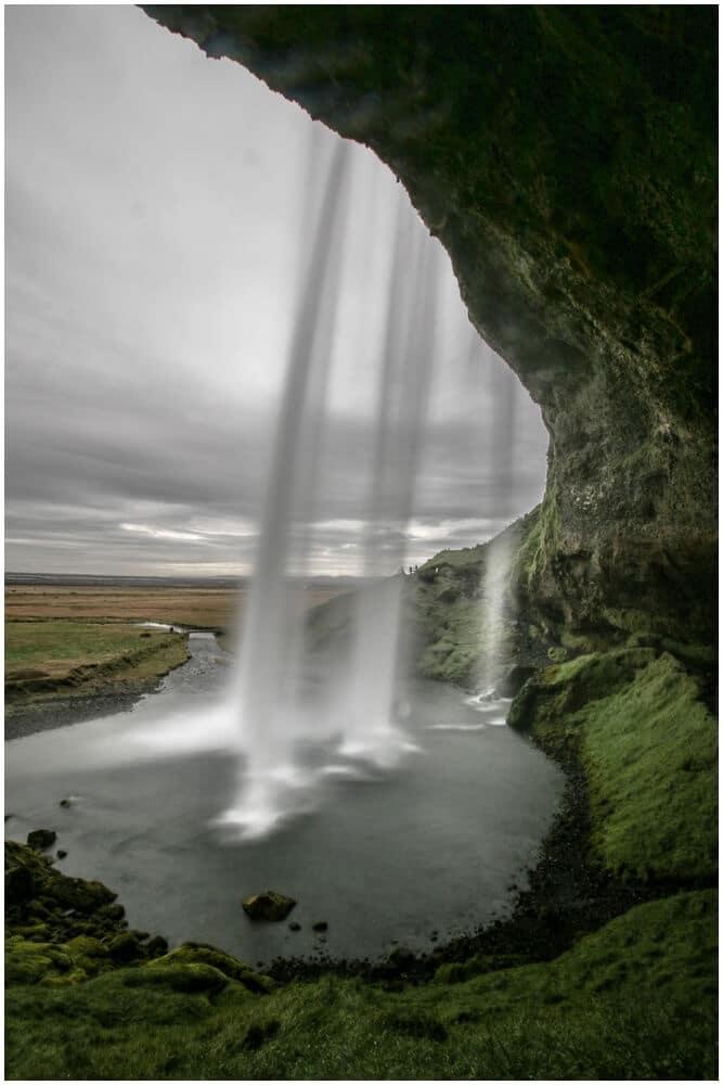 Die Kameralinse ist direkt mit Wassertropfen übersät, wenn man hinter den Wasserfall geht