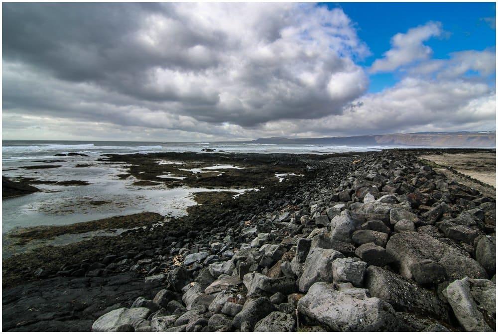 Blick über den Deich bei der Strandarkirkja auf Reykjanesbaer