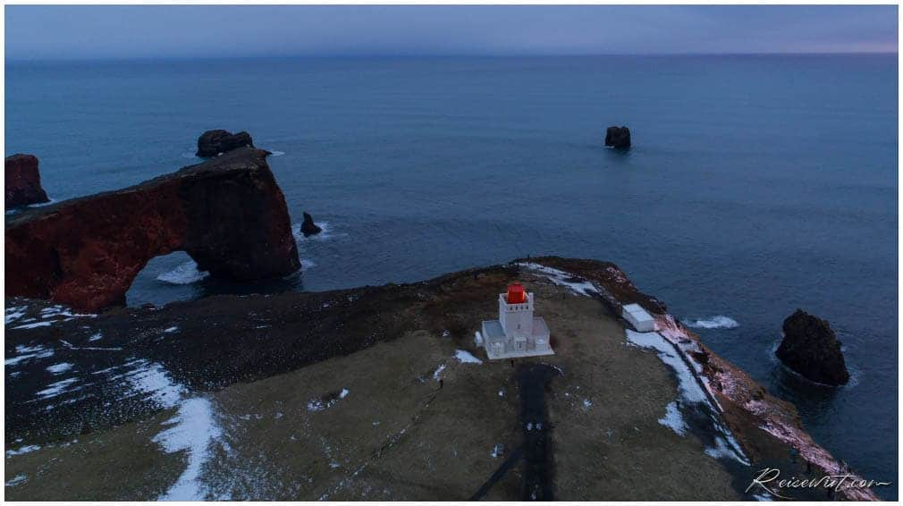 Der Leuchtturm am Kap Dyrhólaey mit dem gewaltige Felsbogen dahinter
