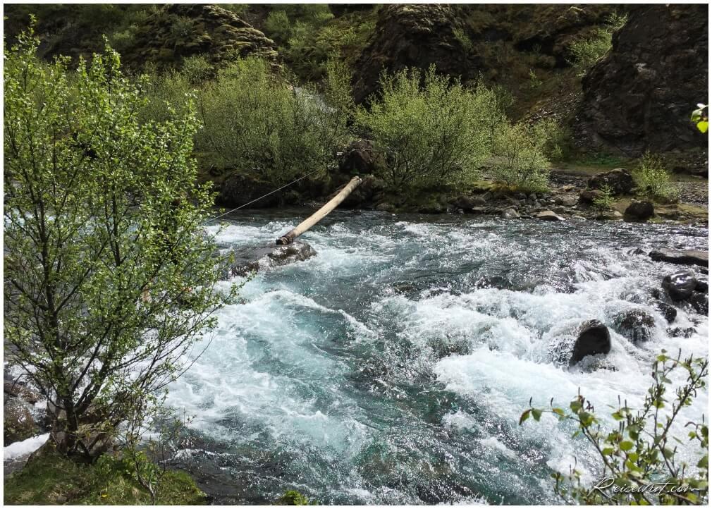 Der Baumstamm über dem Fluss auf dem Glymur Trail