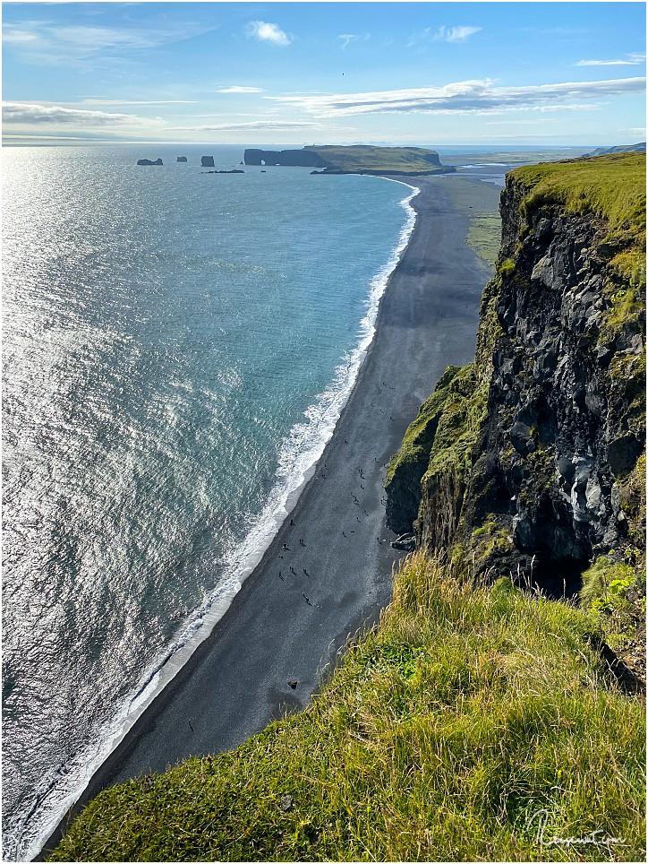 Winzig klein wirken die Besucher unten am Reynisfjara Strand. Der Blickt reicht rüber bis nach Dyrholaey und darüber hinaus