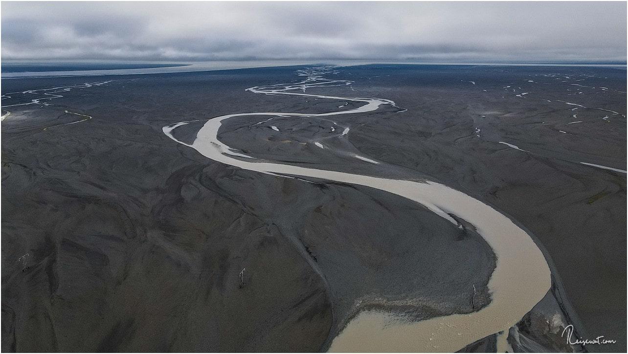 Ein Gletscherfluss sucht sich den Weg durch die Sanderfläche zum Meer