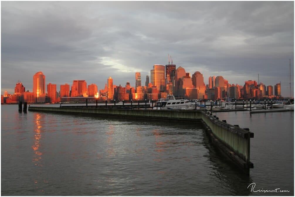 Die Skyline wird von der untergehende Sonne in einem unwirklichen orange angestrahlt. Diesen BLick genießt man vom Jersey Boardwalk in der Nähe des Holland Tunnels