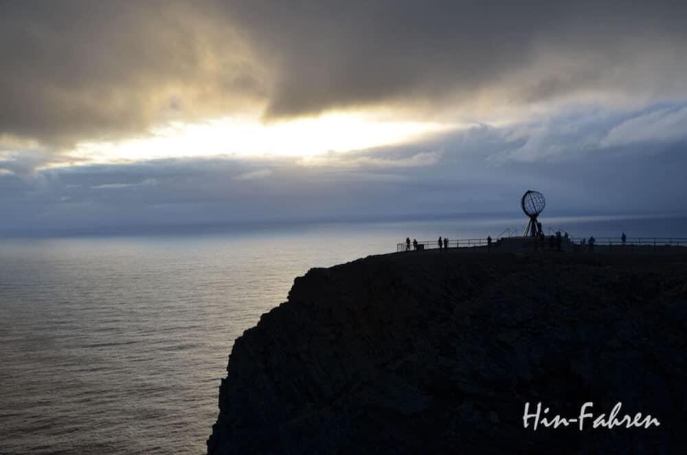Mitternacht am Nordkap. Bei heftigem Sturm reißt kurz die Wolkendecke auf und die Mitternachtssonne erscheint.