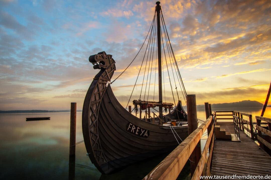 """Sonnenaufgang am Chiemsee mit dem Wikinger Schiff aus dem Film """"Wickie"""" im Vordergrund"""